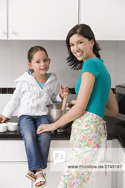 Portrait einer jungen Frau mit ihrer Tochter in einer Küche lächelnd