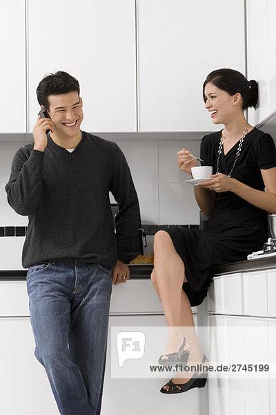 junge Frau hält eine Teetasse mit einem jungen Mann sprechen auf einem Mobiltelefon