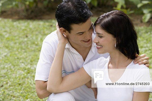 Nahaufnahme eines jungen Paares sitzen in einem Garten und lächelnd
