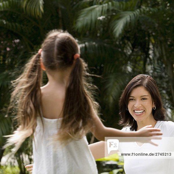 Rückansicht eines Mädchens nach ihrer Mutter in einem Park umarmen