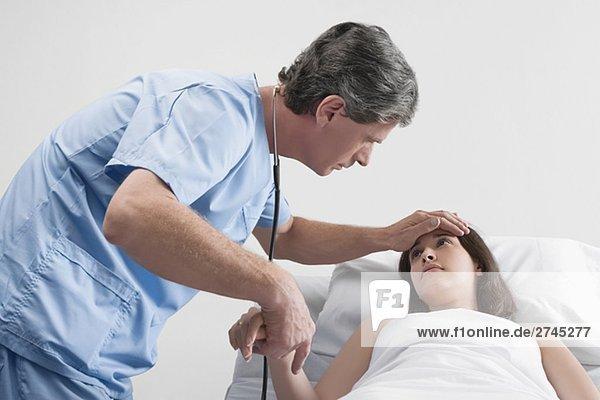 Seitenprofil des männlichen Chirurgen Prüfung einer jungen Frau