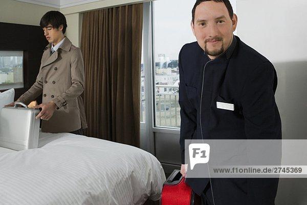 Porträt eines Mannes Zimmerservice hält ein Gepäck mit Blick auf eine Aktentasche Kaufmann