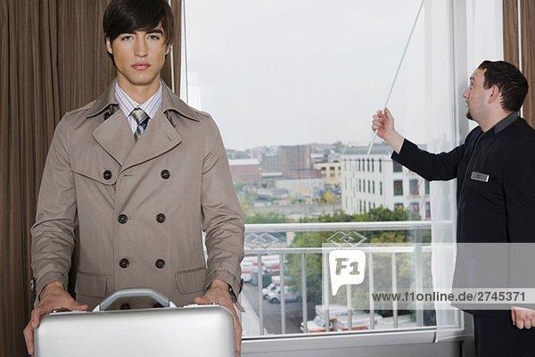 Porträt von ein Unternehmer hält eine Aktentasche mit ein Zimmer Service Mann steht in der Nähe von einem Fenster