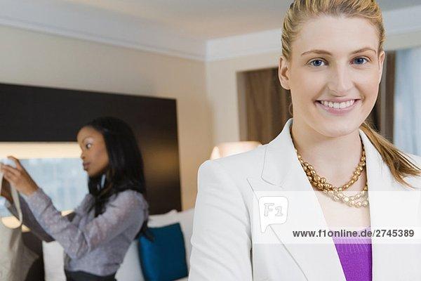 Porträt von geschäftsfrau lächelnd mit einem anderen geschäftsfrau stehen im Hintergrund