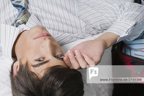 Portrait eines Kaufmanns auf dem Bett liegend