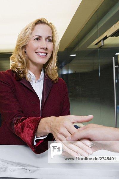 Empfangsdame geben die Cardkey an einem Kunden