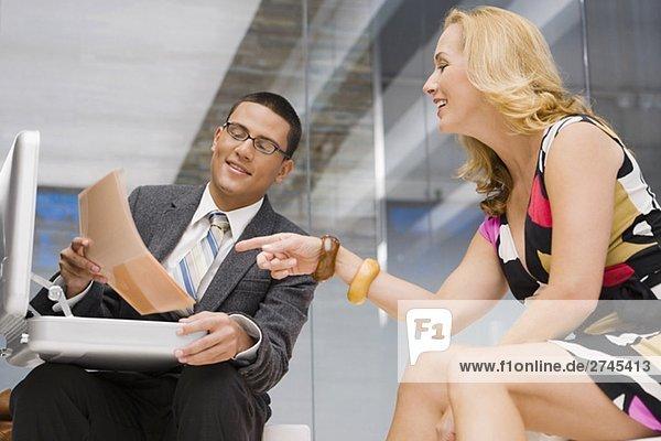 Geschäftsmann  die ein Dokument zu einer Reifen Frau neben ihm sitzt