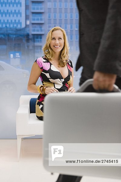 Mature woman sitting on a couch and looking at a man carrying a briefcase