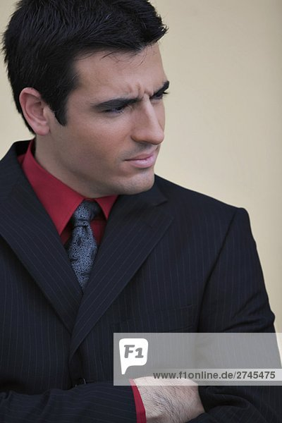 Close-up of a businessman standing with his arms crossed and looking away