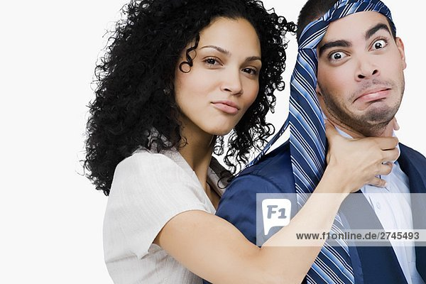Portrait of a businesswoman pretending to strangulate a businessman