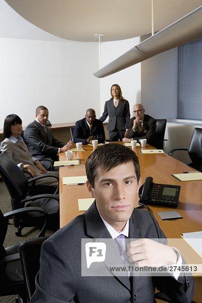 Portrait eines Kaufmanns mit seinen Kollegen im Hintergrund