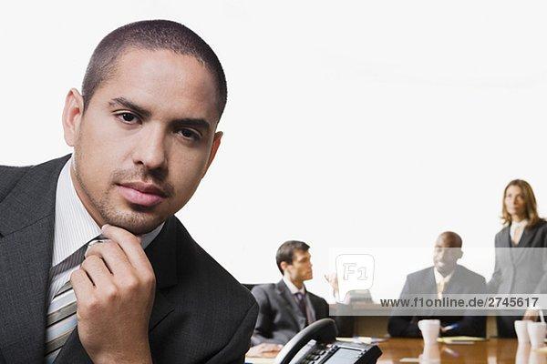 Portrait eines Kaufmanns mit seinen Kollegen diskutieren im Hintergrund