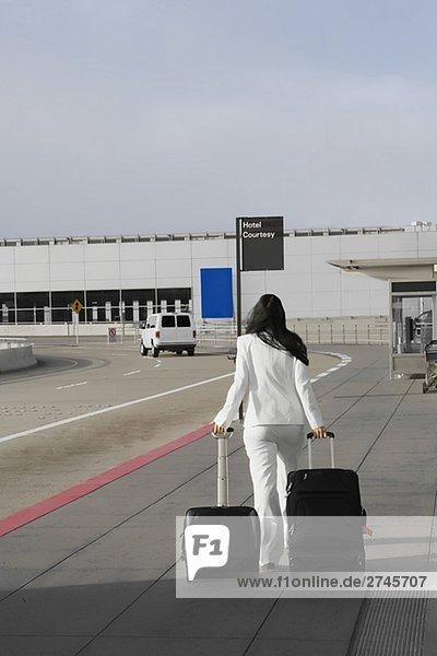 Rückansicht des ziehen ihr Gepäck außerhalb eines Flughafens geschäftsfrau