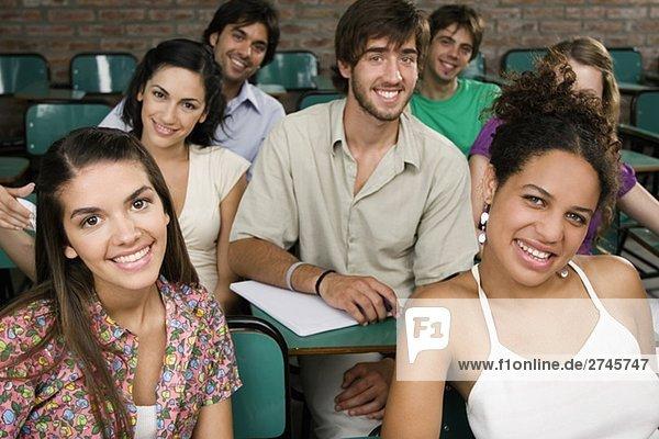 Portrait von Studenten in einem Klassenzimmer sitzen und lächelnd