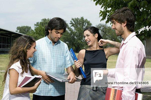 Vier Studenten auf einen Wanderweg stehend und lächelnd