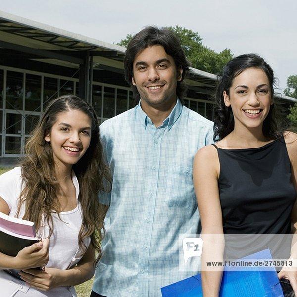 Portrait von drei Studenten zusammen stehen und lächelnd