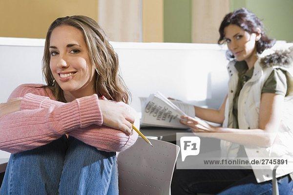 Portrait einer jungen Frau lächelnd mit einer anderen jungen Frau sitzen im Hintergrund