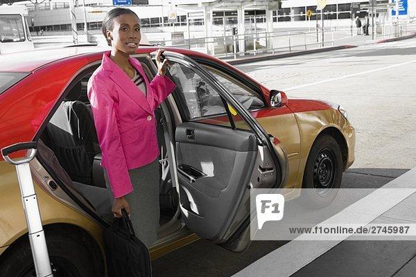 Geschäftsfrau stehen in der Nähe ein Taxi außerhalb auf einem Flughafen