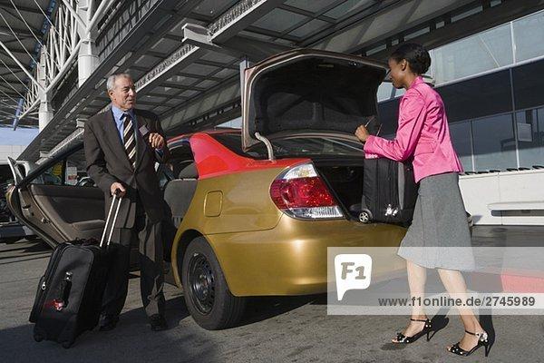 Seitenansicht Laden ihren Koffer auf einem Kofferraum mit einem Geschäftsmann vor ihr stehen geschäftsfrau