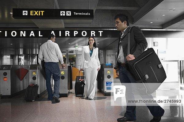 Drei Menschen zu Fuß auf einem Flughafen