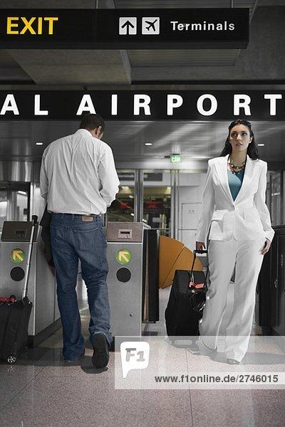 Geschäftsfrau ziehen ihr Gepäck und eine Mitte Erwachsenen Mann Stand in der Nähe ein Check-in Automaten am Flughafen