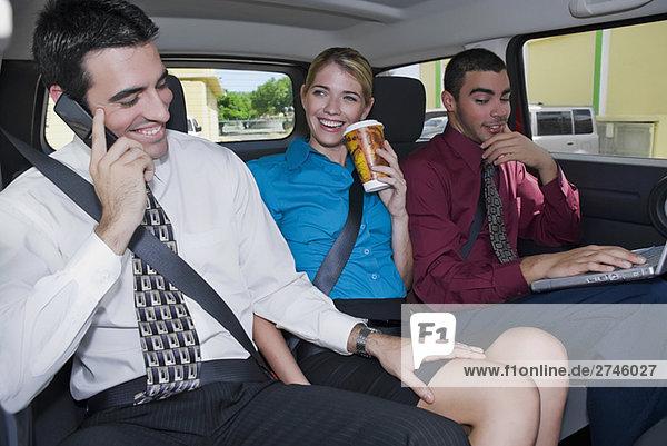Nahaufnahme der Geschäftsfrau sitzt zwischen zwei Geschäftsleute in einem Auto und lächelnd