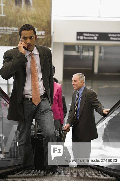 Vier Führungskräfte in Unternehmen stehen auf einer Rolltreppe auf einem Flughafen