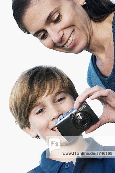 Nahaufnahme einer Mitte erwachsen frau hält eine Digitalkamera und lächelnd mit ihrem Sohn