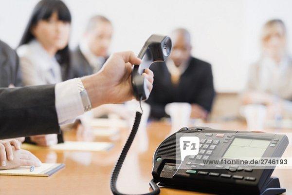 Nahaufnahme ein Geschäftsmann Hand halten einen Konferenz-Telefon-Empfänger
