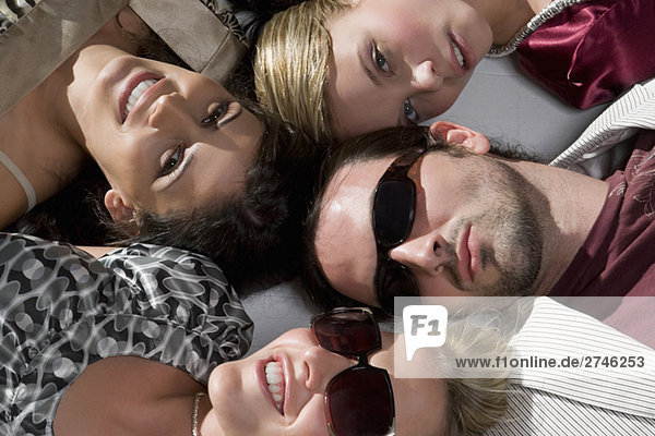 Close-up of a young man with three young women lying down