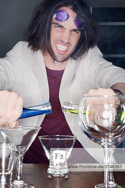 Porträt eines jungen Mannes machen einen cocktail