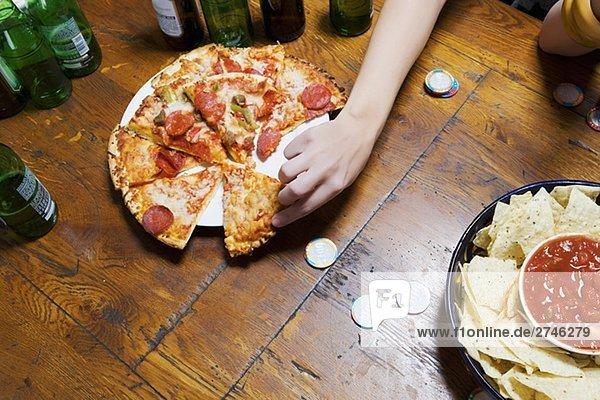 Erhöhte Ansicht einer Person Hand Abholung ein Pizza-slice