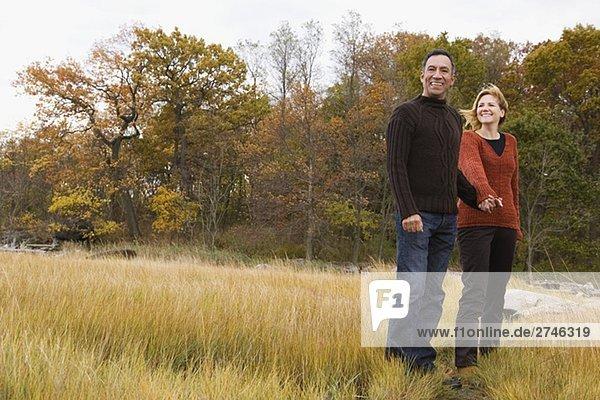reifes Paar stehend auf dem Rasen mit jeweils anderen Hände