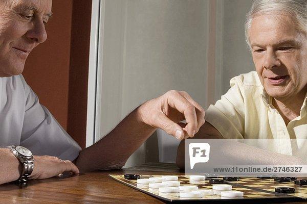 Zwei senior Männer spielen checkers