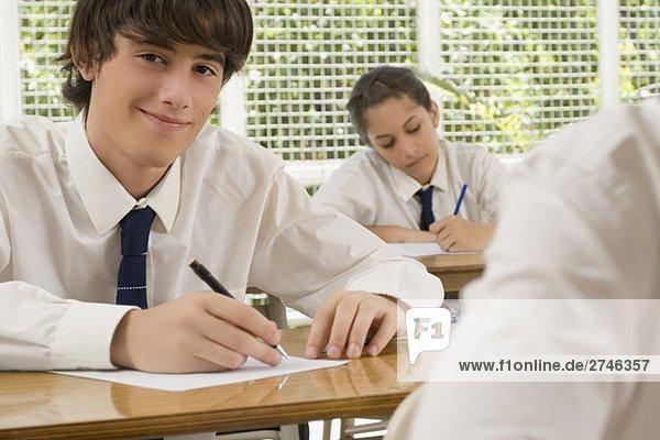 Porträt eines jungen Mannes auf Blatt Papier schreiben und mit einem Teenagerin hinter ihm lächelnd