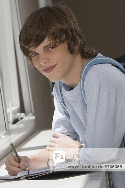 Ein Teenager auf Spiralblock schreiben und lächelnd portrait
