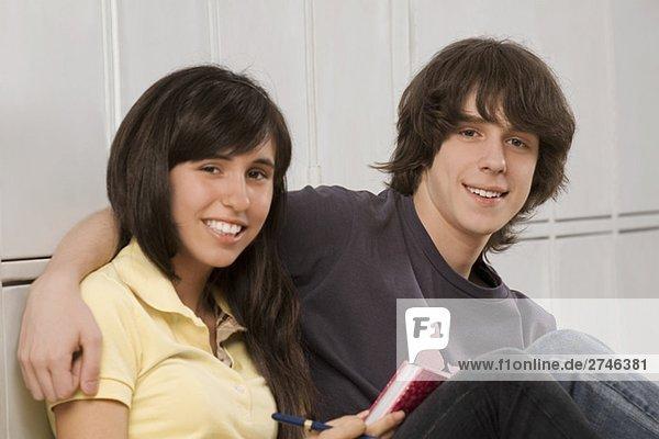 Ein Teenager Porträt mit ein Teenagerin rund um arm und lächelnd