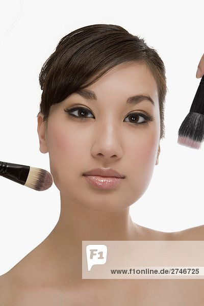 Nahaufnahme of a junge Frau hält Make-up Pinsel und Anwenden von make-up