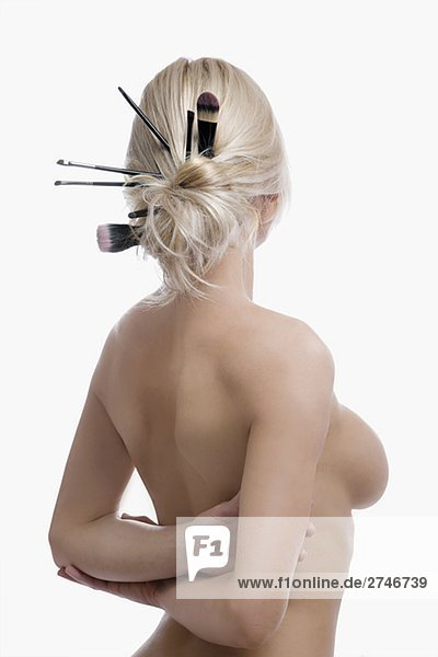 Rückansicht des eine nackte junge Frau mit Make-up Pinsel in ihr Haar-bun