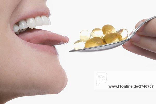 Nahaufnahme einer jungen Frau nehmen einen Löffel Pillen