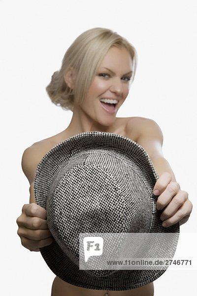 Portrait of a junge Frau hält einen Hut