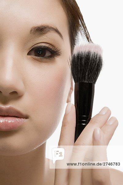 Nahaufnahme of a junge Frau hält einen Make-up-Pinsel