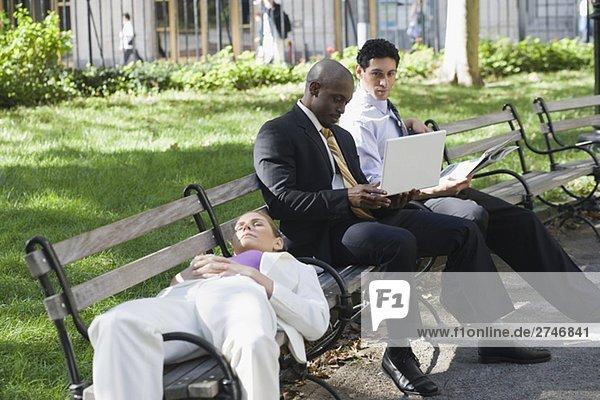 Geschäftsfrau schlafen auf einer Bank mit zwei Geschäftsleute sitzend neben ihr und Blick auf einen laptop