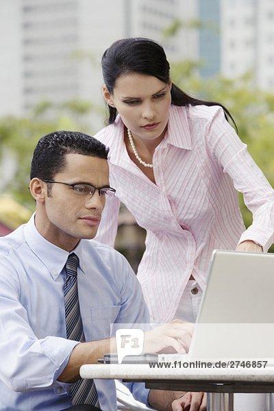 Mit einem Laptop mit stehen neben ihm geschäftsfrau kaufmann