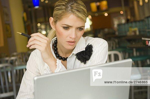 Businesswoman using a laptop in a restaurant