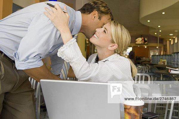 Businessman kissing a businesswoman in a restaurant