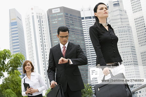 Zwei Unternehmerinnen und Unternehmer walking vor Gebäude