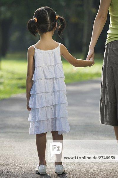 Rückansicht eines Mädchens hält her mother's hand