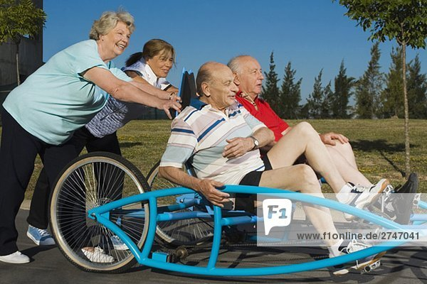 Zwei senior Männer sitzen auf eine Quadracycle und zwei senior DAMENLAUF es