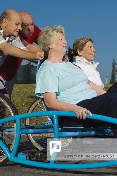 Zwei senior DAMENLAUF sitzt auf einem Quadracycle und zwei senior Männer es